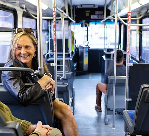 Woman smiling riding the bus while talking to a passenger
