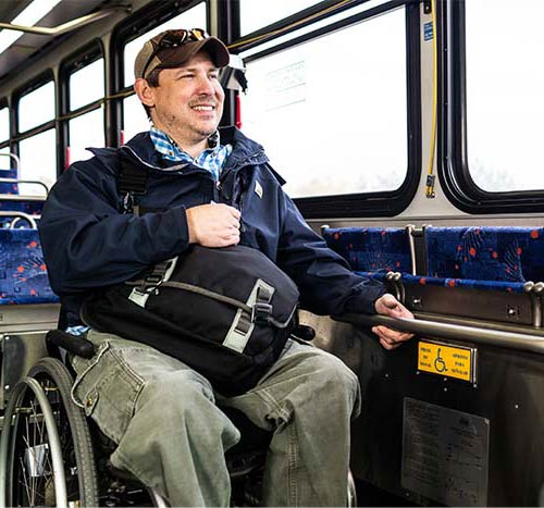 Man wearing a hat, smiling while in his wheelchair riding the bus and holding his personal messenger bag