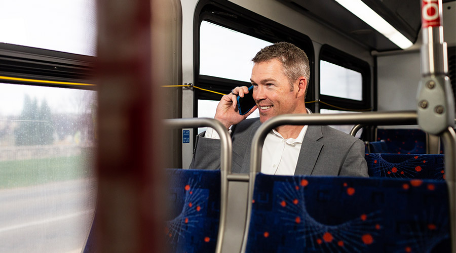 Business talking on his cell phone while riding the bus